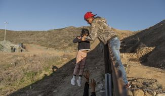 FILE - In this Jan. 3, 2019, file photo, a migrant from Honduras passes a child to her father after he jumped the border fence to get into the U.S. side to San Diego, Calif., from Tijuana, Mexico. The Trump Administration appealed a San Francisco judge's ruling Wednesday, April 10, 2019, that would block it from returning asylum seekers to Mexico to await court hearings. (AP Photo/Daniel Ochoa de Olza, File)