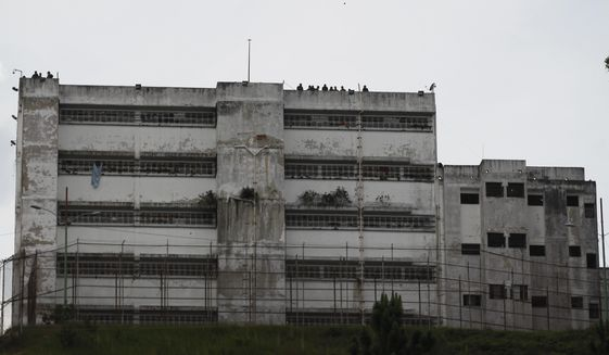 FILE - In this April 28, 2017 file photo, prison guards stand on the roof of the Ramo Verde military prison in Los Teques, on the outskirts of Caracas, Venezuela. The International Committee of the Red Cross has regained access to visit prisons in Venezuela, including highly guarded military facilities such as Ramo Verde where dozens of inmates considered political prisoners are being held. (AP Photo/Ariana Cubillos, File)