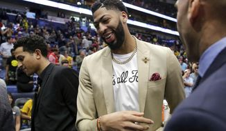 New Orleans Pelicans forward Anthony Davis, wearing a 'That's All Folks,' T-shirt under his jacket, exits the floor, possibly for the last time at a Pelican, after an NBA basketball game against the Golden State Warriors in New Orleans, Tuesday, April 9, 2019. The Warriors won 112-103. (AP Photo/Scott Threlkeld)