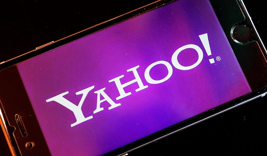 FILE - In this Dec. 15, 2016, file photo, the Yahoo logo appears on a smartphone in Frankfurt, Germany. Nearly 200 million people who had sensitive information snatched from their Yahoo accounts will receive two years of free credit-monitoring services and other potential restitution in a legal settlement valued at $117.5 million. The deal disclosed in documents filed Tuesday, April 9, 2019, revises an earlier agreement struck last October, only to be rejected by U.S. District Court Judge Lucy Koh in San Jose. (AP Photo/Michael Probst, File)