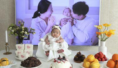 In this April 9, 2019, photo, Lee Dong Kil's daughter Lee Yoon Seol sits to celebrate her the 100th day of the birth at Lee's house in Daejeon, South Korea. Just two hours after Lees daughter was born on New Years Eve, the clock struck midnight, 2019 was ushered in, and the infant became 2-years-old. She wasnt alone, though it happened for her quicker than most: Every baby born in South Korea last year became 2 on Jan. 1.(AP Photo/Ahn Young-joon)
