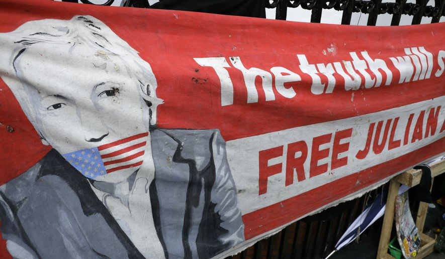A poster displayed on the railings outside the Ecuadorian Embassy in London, after WikiLeaks founder Julian Assange was arrested by officers from the Metropolitan Police and taken into custody Thursday, April 11, 2019. (AP Photo/Matt Dunham)