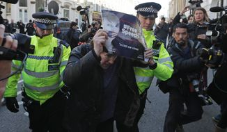 Police officers apprehend a demonstrator outside Westminster magistrates court where WikiLeaks founder Julian Assange was appearing in London, Thursday, April 11, 2019. WikiLeaks founder Julian Assange was forcibly bundled out of the Ecuadorian Embassy in London and into a waiting British police van on Thursday, setting up a potential court battle over attempts to extradite him to the U.S. to face charges related to the publication of tens of thousands of secret government documents. (AP Photo/Frank Augstein)