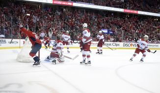 Washington Capitals center Nicklas Backstrom (19), of Sweden, celebrates his goal against Carolina Hurricanes goaltender Petr Mrazek (34), of the Czech Republic, defenseman Brett Pesce (22) and others during the first period of Game 1 of an NHL hockey first-round playoff series Thursday, April 11, 2019, in Washington. The Capitals won 4-2. (AP Photo/Nick Wass)