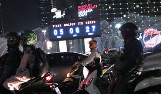 Motorists stop at a traffic light near a digital display showing the countdown timer to the presidential and legislative elections in Jakarta, Indonesia, Thursday, April 11, 2019. Indonesia's Election Commission said Thursday it was sending officials to investigate after videos circulated online of thousands of voting papers for next week's polls scattered throughout a warehouse in neighboring Malaysia. (AP Photo/Dita Alangkara)