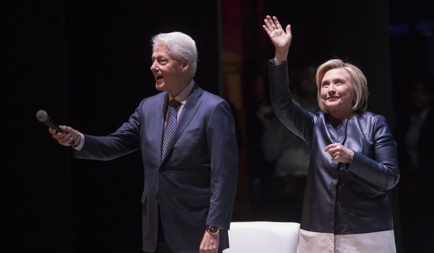 """Former President Bill Clinton, left, and former Secretary of State Hillary Rodham Clinton wave at the crowd as they arrive on stage for """"An Evening with the Clintons,"""" at the Beacon Theatre Thursday, April 11, 2019, in New York. (AP Photo/Mary Altaffer)"""
