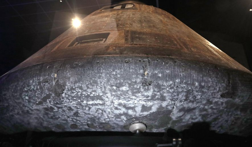 The NASA Apollo 11 command module Columbia, its bottom scorched and pitted from reentry into Earth's atmosphere decades earlier, sits as the centerpiece of Destination Moon: The Apollo 11 Mission exhibit at the Museum of Flight, Thursday, April 11, 2019, in Seattle. The exhibit, opening April 13, celebrates the 50th anniversary of the U.S. manned moon landing on July 20, 1969. The exhibit includes artifacts from the Apollo 11 mission, including Buzz Aldrin's outer visor and gloves worn while walking on the moon, a star chart, medical kit and survival kit (for an emergency landing on Earth). The display also includes a full-scale replica of the lunar module ascent vehicle and salvaged F-1 engine parts, which powered the Saturn V rocket that took the Apollo modules to space and were recovered from the Atlantic ocean more than 40 years later. (AP Photo/Elaine Thompson)