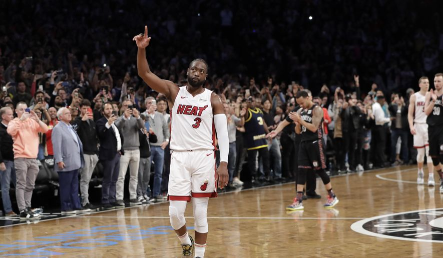 Miami Heat guard Dwyane Wade (3) acknowledges the crowd's cheers after playing in the final NBA basketball game of his career, against the Brooklyn Nets on Wednesday, April 10, 2019, in New York. (AP Photo/Kathy Willens) ** FILE **