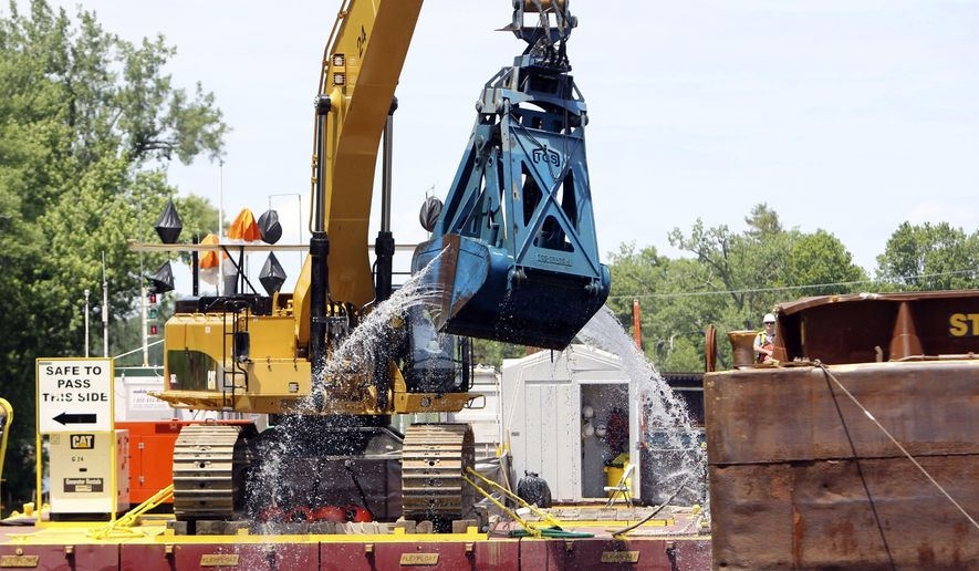 FILE - In this June 10, 2011 file photo, crews dredge the Hudson River in Fort Edward, N.Y. The work is part of a project on the upper-Hudson to clean up PCBs released by General Electric decades ago. The Environmental Protection Agency is poised to make an announcement Thursday, April 11, 2019, on GE's $1.7 billion Hudson River cleanup. (AP Photo/Mike Groll, File)