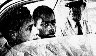 CORRECTS SPELLING OF LAST NAME TO HURT, NOT HUNT - FILE - In this Feb. 1964 file photo, Henry Montgomery, flanked by two deputies, awaits the verdict in his trial for the murder of Deputy Sheriff Charles H. Hurt in Baton Rouge, La. A three-member board will hear the case of Henry Montgomery on Thursday, April 11, 2019. The 72-year-old Montgomery was convicted of killing Hurt in 1963. Montgomery was 17 at the time. (John Boss/The Advocate via AP, File)