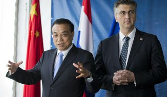 """China's Premier Li Keqiang, left, and Croatia's Prime Minister Andrej Plenkovic gesture after symbolically starting a machine at the construction site of a bridge built by a Chinese company and largely EU founded, in Brijesta, Southern Croatia, Thursday, April 11, 2019.  Croatia is hosting a summit on Thursday for China and 16 European countries that endorsed Beijing's global """"Belt and Road"""" initiative. (AP Photo/Darko Bandic)"""