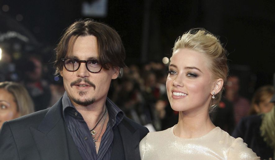 """In this Nov. 3, 2011, file photo, U.S. actors Johnny Depp, left, and Amber Heard arrive for the European premiere of their film, """"The Rum Diary,"""" in London. Heard is asking a judge to dismiss a $50 million defamation lawsuit her ex-husband Johnny Depp filed over a Washington Post op-ed she wrote about domestic violence. (AP Photo/Joel Ryan, File)"""