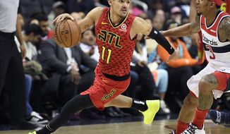 """FILE - In this Feb. 4, 2019, file photo, Atlanta Hawks guard Trae Young (11) dribbles the ball against Washington Wizards guard Bradley Beal (3) during the second half of an NBA basketball game, in Washington. A 29-win season may not look like much on paper, but first-year coach Lloyd Pierce says huge goals of establishing an identity and culture were """"home runs"""" for the team. At the core of the growth was rookie point guard Trae Young. (AP Photo/Nick Wass, File+)"""