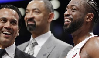 Miami Heat coach Erik Spoelstra, left, and guard Dwyane Wade, right, smile during the second half of the team's NBA basketball game against the Brooklyn Nets, Wednesday, April 10, 2019, in New York. It was the final NBA game of Wade's career. Assistant coach Juwan Howard is at rear. (AP Photo/Kathy Willens)