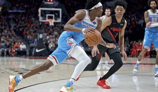 Sacramento Kings guard De'Aaron Fox, left, drives to the basket in front of Portland Trail Blazers guard Anfernee Simons during the first half of an NBA basketball game in Portland, Ore., Wednesday, April 10, 2019. (AP Photo/Craig Mitchelldyer)