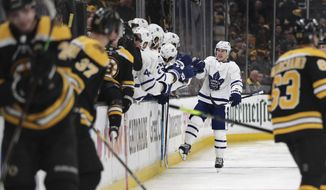 Toronto Maple Leafs right wing Mitchell Marner, right rear, is congratulated by teammates after his penalty-shot goal off Boston Bruins goaltender Tuukka Rask during the second period of Game 1 of an NHL hockey first-round playoff series Thursday, April 11, 2019, in Boston. (AP Photo/Charles Krupa)
