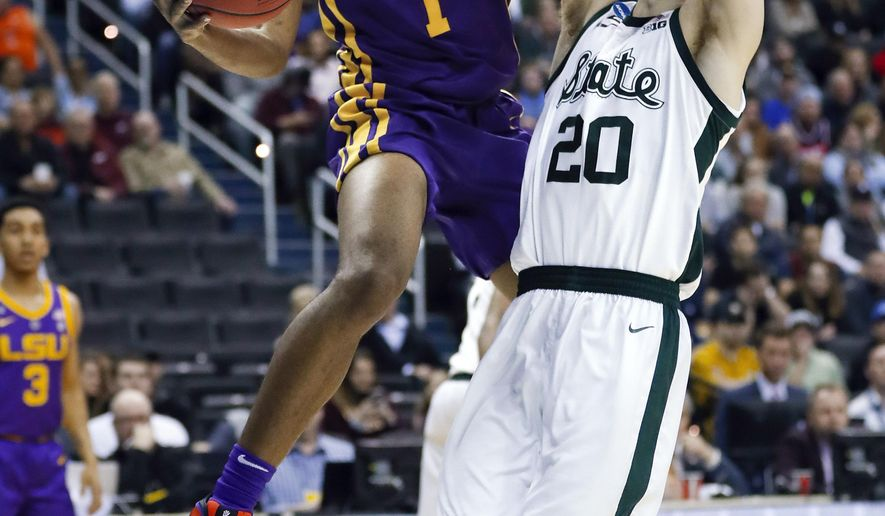 LSU guard Javonte Smart looks to pass the ball as Michigan State guard Matt McQuaid (20) defends during the first half of an NCAA men's college basketball tournament East Regional semifinal in Washington, Friday, March 29, 2019. (AP Photo/Patrick Semansky)