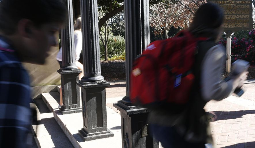FILE- In this Jan. 9, 2019, file photo University of Georgia undergraduate students avoid walking under the university arch on the first day of the spring semester in Athens, Ga. As the U.S. student loan balance surpasses $1.5 trillion, a trio of contests promise a lucky few a shot at putting a dent in their debt. (Joshua L. Jones/Athens Banner-Herald via AP)