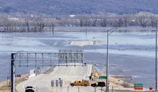 In this March 16, 2019 photo, Neb. Department of Roads crews block the flooded highway 34 that connects Platteview, Neb., to I-29 in Iowa. Iowa and Nebraska transportation officials say they're hoping to have nearly all roads and bridges damaged in the wake of massive flooding last month repaired by midsummer, but they note that wet weather this spring could hamper that effort. (AP Photo/Nati Harnik)