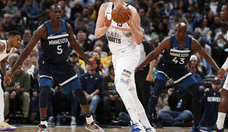 Denver Nuggets center Nikola Jokic, center, looks to pass the ball as Minnesota Timberwolves center Gorgui Dieng, left, and Anthony Tolliver defend during the first half of an NBA basketball game Wednesday, April 10, 2019, in Denver. (AP Photo/David Zalubowski)