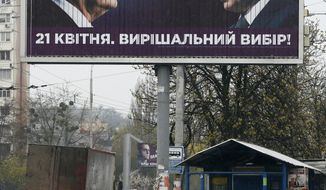 """People pass by a billboard depicting Ukraine's President Petro Poroshenko and Russian President Vladimir Putin looking at each other in Kiev, Ukraine, Thursday, April 11, 2019. Writing on the big board reads: """"A decisive choice."""" Poroshenko is running for his second term at the second round of presidential vote on April 21. He advocates Ukraine's integration into the European Union back from Russian influence. (AP Photo/Efrem Lukatsky)"""