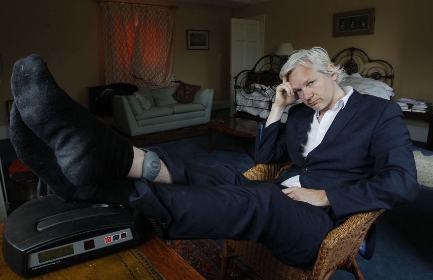 FILE - In this Wednesday, June 15, 2011 file photo, WikiLeaks founder Julian Assange is seen with his ankle security tag at the house where he is required to stay, near Bungay, England. Police in London arrested WikiLeaks founder Assange at the Ecuadorean embassy Thursday, April 11, 2019 for failing to surrender to the court in 2012, shortly after the South American nation revoked his asylum. (AP Photo/Kirsty Wigglesworth, file)
