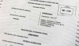 The Grand Jury Indictment against Julian Assange, released by the U.S. Department of Justice, Thursday, April 11, 2019, is photographed in Washington.  The U.S. Justice Department has charged WikiLeaks founder Julian Assange with conspiring with Chelsea Manning to break into a classified government computer. (AP Photo/Wayne Partlow)