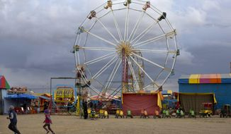 Children run through the midway as workers slowly help fairgoers off a Ferris wheel at the 'Feria de Ramos' or Palm Fair, in El Alto, Bolivia, Thursday, April 11, 2019. Thousands of indigenous people mark Palm Sunday with an annual agricultural fair in the suburbs of one of Bolivia's largest cities. The so-called Palm Sunday Fair, which began as a way to recreate the livestock markets of biblical times, is currently dominated by all sorts of informal trade and a midway. (AP Photo/Juan Karita)