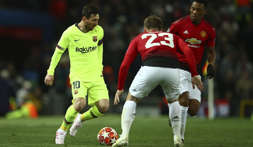 Barcelona's Lionel Messi, left, challenges with Manchester United's Luke Shaw during the Champions League quarterfinal, first leg, soccer match between Manchester United and FC Barcelona at Old Trafford stadium in Manchester, England, Wednesday, April 10, 2019. (AP Photo/Dave Thompson)