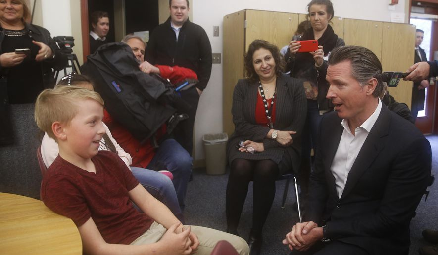 "FILE - In this Feb. 14, 2019 file photo Gov. Gavin Newsom talks with Jake Boykis, 10, left, who lost his home in last years Camp Fire, during a visit to the Pine Ridge Elementary School, in Magalia, Calif. Newsom plans to present, Friday, April 12, 2019, a report offering ideas for California to deal with Pacific Gas & Electric Corp.'s bankruptcy and the growing cost of wildfires. The report is the work of a ""strike team"" Newsom created in the wake of the bankruptcy. (AP Photo/Rich Pedroncelli, File)"