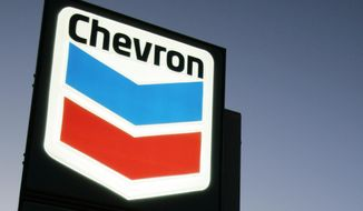 FILE - In this file photograph taken July 25, 2007, a Chevron gas station service sign is displayed in Menlo Park, Calif.  Chevron is buying Anadarko Petroleum in a cash-and-stock deal valued at $33 billion that'll help strengthen its position in shale, deepwater and natural gas resource basins.  Chevron and Anadarko said Friday, April 12, 2019 that the deal will create a 75-mile-wide corridor across the most attractive acreage in the Delaware basin; bolster Chevron's position in the Gulf of Mexico and add a resource base in Mozambique to support growing LNG demand. (AP Photo/Paul Sakuma, file)