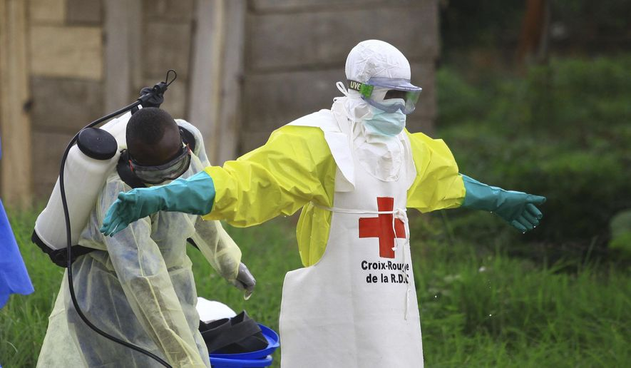 """In this Sunday, Sept 9, 2018, photo, a health worker sprays disinfectant on his colleague after working at an Ebola treatment center in Beni, eastern Congo. Top Red Cross official Emanuele Capobianco said April 12, 2019, that he's """"more concerned than I have ever been"""" about the possible regional spread of the Ebola virus in Congo after a recent spike in cases. (AP Photo/Al-hadji Kudra Maliro) **FILE**"""