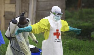"In this Sunday, Sept 9, 2018, photo, a health worker sprays disinfectant on his colleague after working at an Ebola treatment center in Beni, eastern Congo. Top Red Cross official Emanuele Capobianco said April 12, 2019, that he's ""more concerned than I have ever been"" about the possible regional spread of the Ebola virus in Congo after a recent spike in cases. (AP Photo/Al-hadji Kudra Maliro) **FILE**"