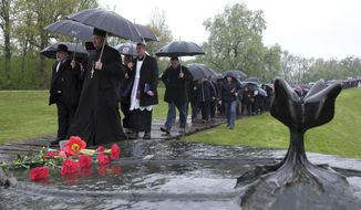 Hundreds gather at the memorial center to pay their respects for tens of thousands of people killed in death camps run by Croatia's pro-Nazi puppet state in WWII, in Jasenovac, Croatia, Friday, April 12, 2019.  Croatia's Jewish, Serb, anti-fascist and Roma groups have commemorated the victims of a World War II death camp, snubbing the official ceremonies for the fourth year in a row over what they say is government inaction to curb neo-Nazi sentiments in the European Union country. (AP Photo/Nikola Solic)