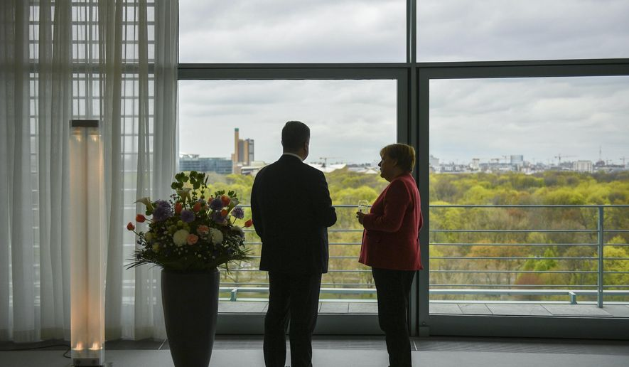 German Chancellor Angela Merkel, right, and the President of Ukraine Petro Poroshenko are talking during a meeting in Berlin, Germany, Friday, April 12, 2019. (Mykola Lazarenko/Presidential Press Service Pool Photo via AP)