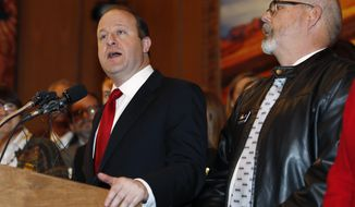 """Colorado Gov. Jared Polis, left, speaks as Rep. Tom Sullivan, D-Aurora, looks on before Polis signs a bill to allow Colorado to become the 15th state in the union to adopt a """"red flag"""" gun law allowing firearms to be taken from people who pose a danger during a ceremony Friday, April 12, 2019, in the State Capitol in Denver. (AP Photo/David Zalubowski)"""