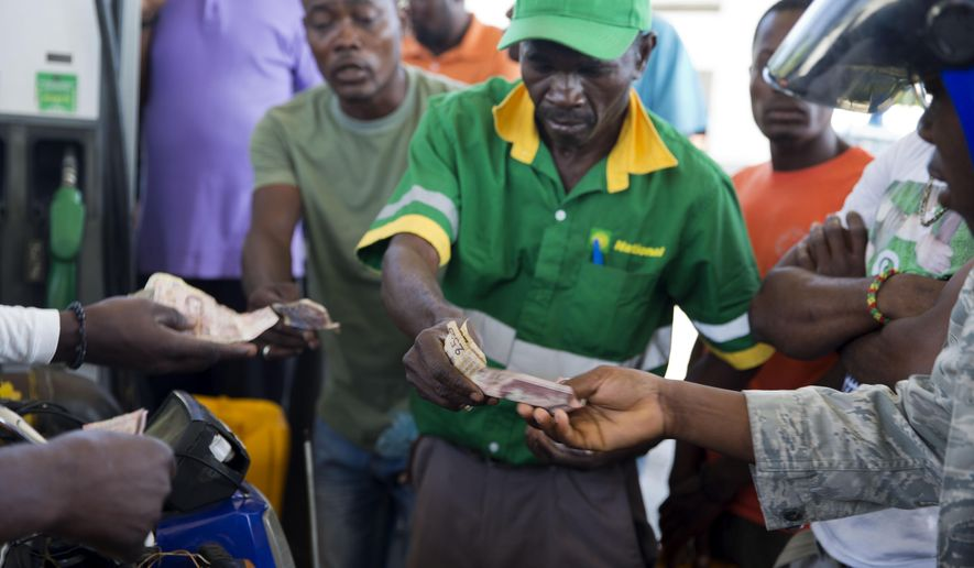 A gas station attendant collects money and gives back change during a two-week-long fuel shortage as customers buy fuel in Port-au-Prince, Haiti, Wednesday, April 10, 2019. Haiti's government, which subsidizes fuel, plans to open the gasoline market to the private sector in order to ease the shortage, according to Haiti's Director General of the Office of Monetization and Development Assistance Program Ignace Saint-Fleur, speaking to a local radio station on Monday. (AP Photo/Dieu Nalio Chery)