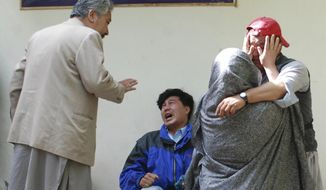 Family members of the blast victims comfort each other outside a mortuary in Quetta, Pakistan, Friday, April 12, 2019. A powerful bomb went off at an open-air market in the southwestern city of Quetta on Friday, police and hospital officials said. (AP Photo/Arshad Butt)