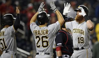 Pittsburgh Pirates' Colin Moran (19) celebrates his three-run home run with Adam Frazier (26) and Jason Martin (51) during the 10th inning of a baseball game against the Washington Nationals, Friday, April 12, 2019, in Washington. (AP Photo/Nick Wass)