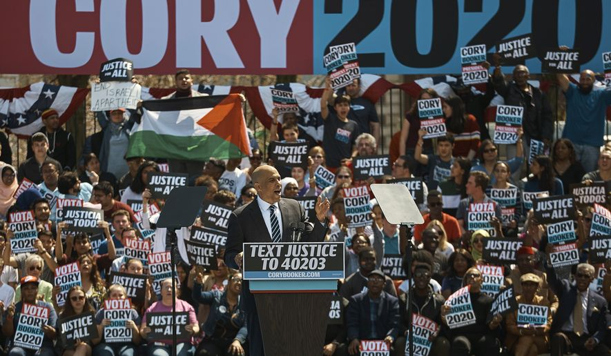 """A man display a Palestinian flag as a woman shows a banner reading """"End Israeli Apartheid"""" while Cory Booker talks to the crowd during a hometown kickoff for his national presidential campaign tour at Military Park in downtown Newark, N.J., Saturday, April 13, 2019. (AP Photo/Andres Kudacki)"""