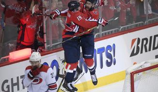 Washington Capitals right wing Tom Wilson (43) celebrates his goal with center Nicklas Backstrom (19), of Sweden, during the third period of Game 2 of an NHL hockey first-round playoff series as Carolina Hurricanes defenseman Brett Pesce (22) skates away, Saturday, April 13, 2019, in Washington. (AP Photo/Nick Wass) ** FILE **