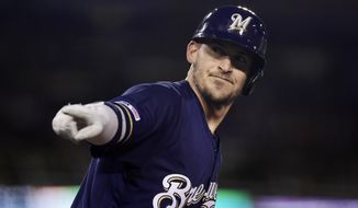 Milwaukee Brewers' Yasmani Grandal points to his dugout after hitting a two-run home run during the fifth inning of the team's baseball game against the Los Angeles Dodgers on Friday, April 12, 2019, in Los Angeles. (AP Photo/Mark J. Terrill)