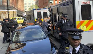 Police bundle WikiLeaks founder Julian Assange, center right, from the Ecuadorian embassy into a police van in London after he was arrested by officers from the Metropolitan Police and taken into custody Thursday April 11, 2019. Police in London arrested WikiLeaks founder Assange at the Ecuadorean embassy Thursday for failing to surrender to the court in 2012, shortly after the South American nation revoked his asylum. (@DailyDOOH via AP)