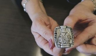 In this March 3, 2019 photo, Julie Kavanaugh, formerly an administrator with the Chicago Blackhawks, holds her Stanley Cup ring in Ashland, Ky. Kavanaugh received the ring during her time with NHL hockey club. She is now an employee of Braidy Industries. (Glenn Puit/The Daily Independent via AP)