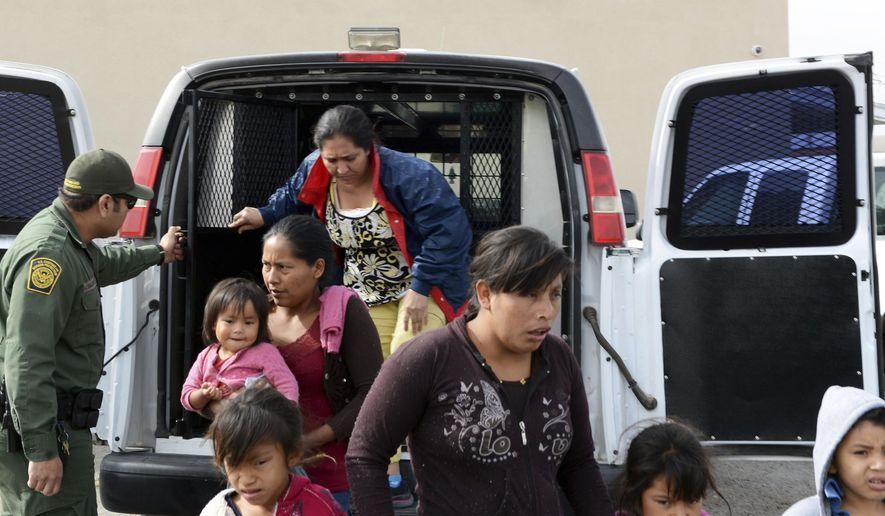 In this Friday, April 12, 2019 photo, a U.S. Border Patrol agent helps migrants out of a van at the Gospel Rescue Mission in Las Cruces, N.M. The U.S. Border Patrol agents dropped off asylum-seeking migrants in New Mexico's second most populous city for the second day in a row Saturday, April 13, 2019 prompting Las Cruces city officials to appeal for donations of food and personal hygiene items. The migrants were being temporarily housed at a homeless shelter, a city recreation center and a campus of social service agencies. (Blake Gumprecht/The Las Cruces Sun News via AP)