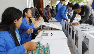 Indonesian electoral volunteers prepare ballot boxes to be distributed to polling stations in Bali, Indonesia, Saturday, April 13, 2019. The world's third-largest democracy is gearing up to hold its legislative and presidential elections on April 17. (AP Photo/Firdia Lisnawati)