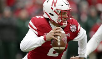 FILE -  In this file Nov. 17 2018, photo, Nebraska quarterback Adrian Martinez scrambles away from a Michigan State defender during an NCAA college football game in Lincoln, Neb. Martinez exceeded the hype that followed him from Fresno, Calif., to Lincoln as coach Scott Frost's first recruit. He was the first true freshman quarterback to start a season opener for the Cornhuskers and became the most productive rookie in program history. (AP Photo/Nati Harnik)