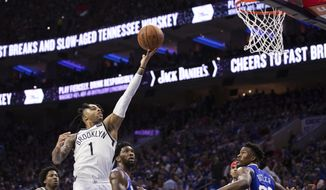 Brooklyn Nets' D'Angelo Russell, left, goes up for the shot as he gets past Philadelphia 76ers' Joel Embiid, center, of Cameroon, during the second half in Game 1 of a first-round NBA basketball playoff series, Saturday, April 13, 2019, in Philadelphia. The Nets won 111-102. (AP Photo/Chris Szagola)