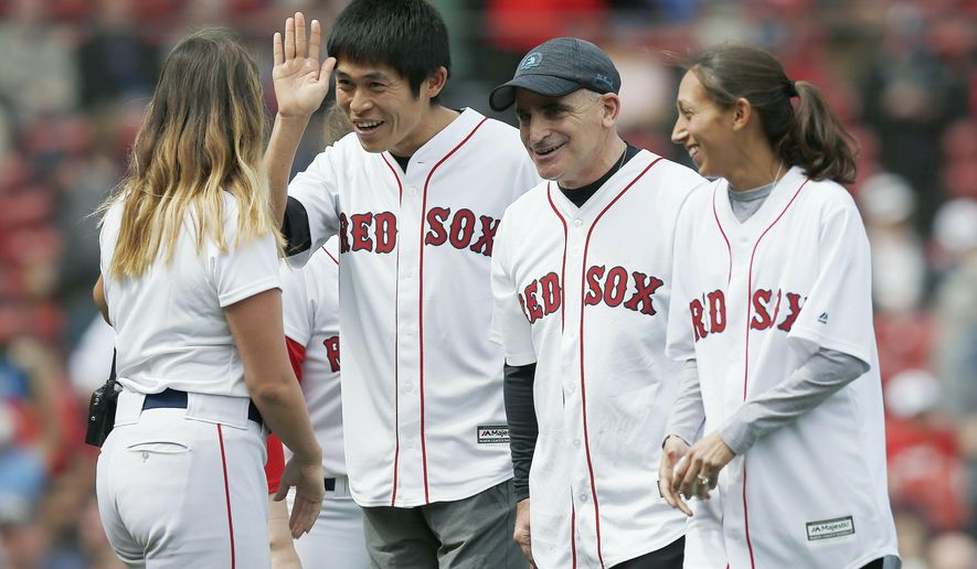 2018 Boston Marathon winners Yuki Kawauchi, left, and Desiree Linden, right, walk off the field with race sponsor John Hancock's Rob Freidman, center, after throwing out the ceremonial first pitch before a baseball game between the Boston Red Sox and the Baltimore Orioles in Boston, Saturday, April 13, 2019. (AP Photo/Michael Dwyer)