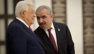 Palestinian Prime Minister Mohammad Ishtayeh, right, talks with Palestinian President Mahmoud Abbas during a swearing in of the new government in the West Bank city of Ramallah, Saturday, April 13, 2019.(AP Photo/Majdi Mohammed)